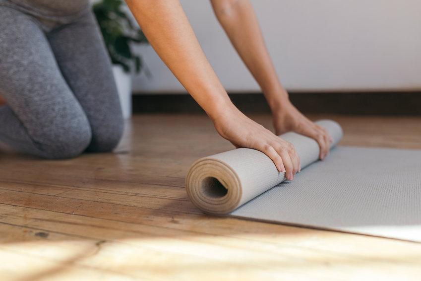 rolling-out-a-yoga-mat-UXEK8YL.jpg