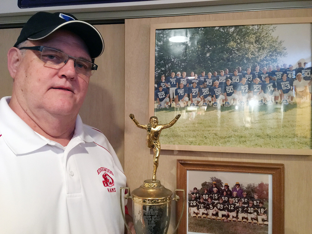 A long-time football and lacrosse coach at Kenwood and Edgewood, Fred Myers, the 1968 Unsung Hero winner, shows off his trophy and watch while standing next to a photo of his 1995 Kenwood team. No. 55 in that photo is Earl Henson, who also won the top prize at the Unsung Hero banquet.
