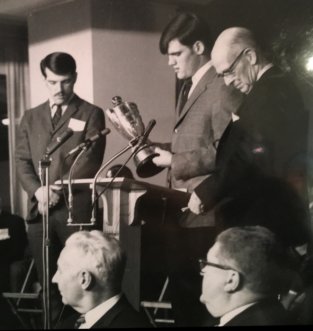 Flanked by his late brother Tom (left), Fred Myers takes to the podium for his acceptance speach, shortly after he was named the McCormick Unsung Hereo Award winner in 1968, by Charles P. McCormick (right).