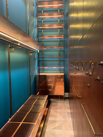 tailor made walk in wardrobe with tan leather topped shelves and  and copper fixtures