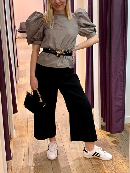 blonde styling client wearing big puffed sleeve top with vintage belt and wide leg crop trousers and  sneakers