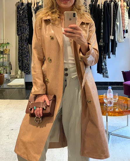 girl wearing luxurious stylish sand coloured leather coat with neutral balloon trousers and cool clutch bag
