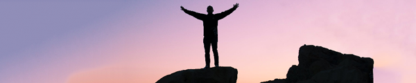 Hero image of a person standing on top of a rock formation and his arms stretched out wide triumphantly