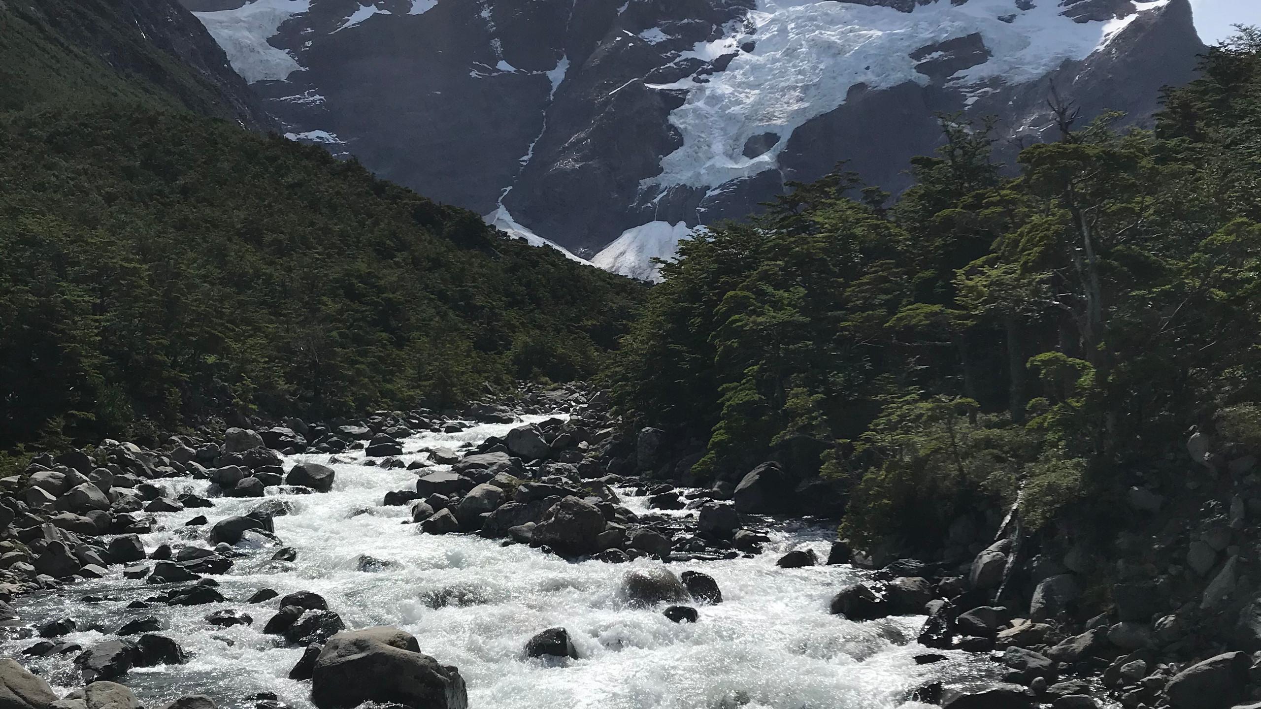 Wanderweg zum Torres del Paine mit Flussquellen und einer Schneelandschaft im Hintergrund