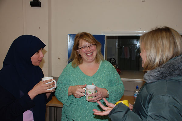 Three ladies happily chatting whilst drinking cups of tea