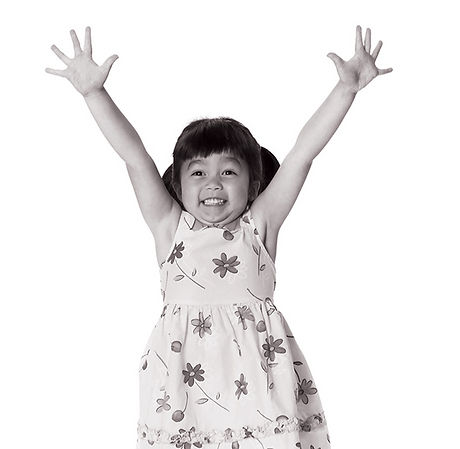 Little girl wearing a flower patterned dress jumping with her hands in the air