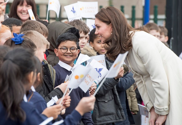 The Duchess of Cambridge is leant forward talking to a group of school children. They are holding flags.