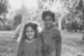 Two little girls stood together smiling, with trees in the background