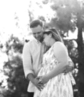 Husband embracing pregnant wife, with his hand resting on her baby bump
