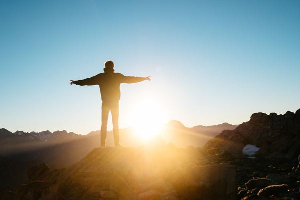 Man stood on a rocky hillside, looking out to the view. The sun is setting, over the hills in the distance