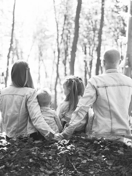 Mother, Father, with their two children sit holding hands looking out to the trees.