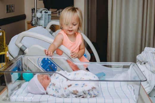 Big sister looking down at newborn baby borther at Women Clinic Saddleback Memorial Hospital-Doctor Raffo-Bug and Roo Photography-Fresh 48 Photographer-Laguna Hills-Orange County