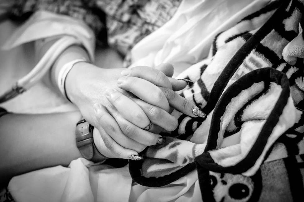 Dad holding mom's hand while in labor at Hoag Hospital-Bug and Roo Photography-Birth Photographer-Newport Beach, Orange County