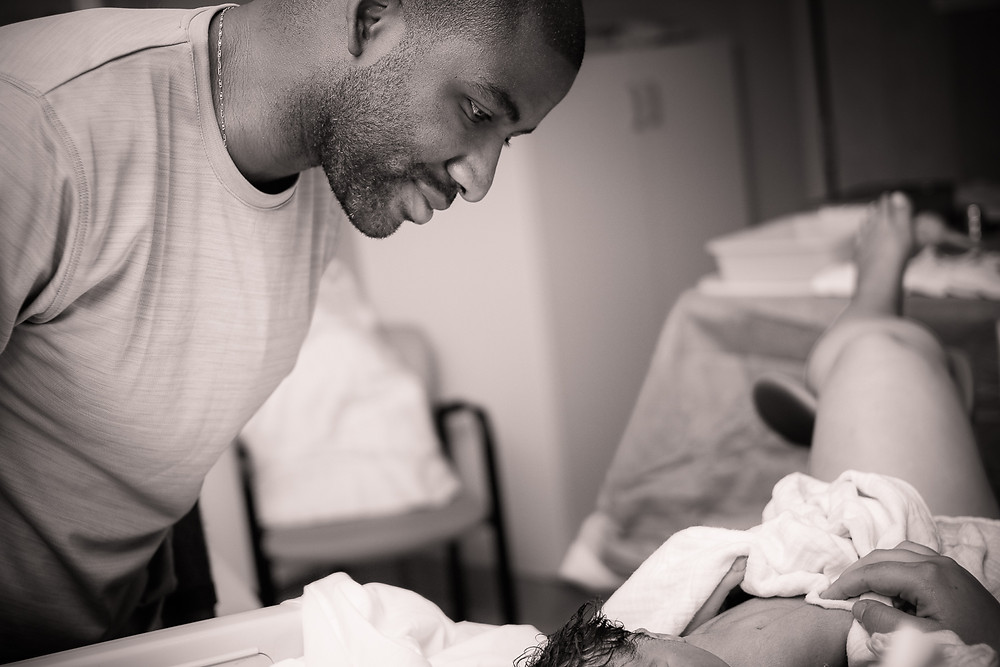 Dad looking at newborn baby sleeping on mom's chest after VBAC delivery at Kaiser Hospital in Irvine California | Bug and Roo Photography | Birth Photographer | Orange County
