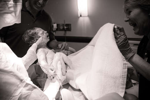 newborn baby being given to mom after de