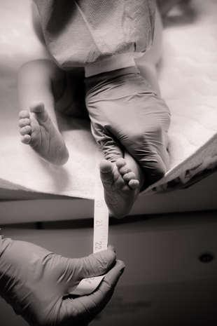 newborn baby getting measured after birt
