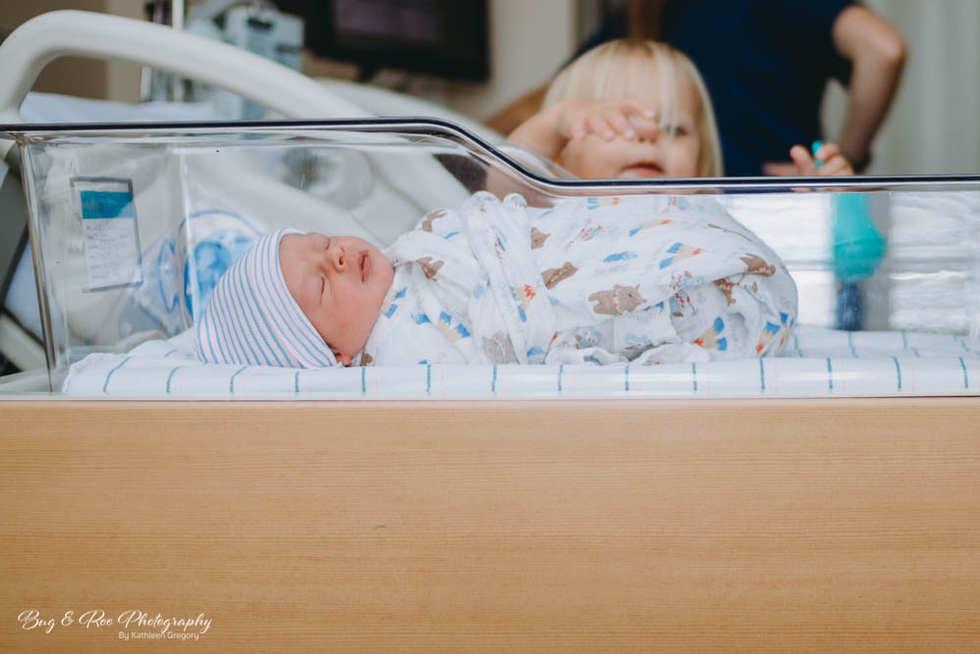 Big sister grabbing for baby brother in bassinet at Women Clinic Saddleback Memorial Hospital-Doctor Raffo-Bug and Roo Photography-Fresh 48 Photographer-Laguna Hills-Orange County