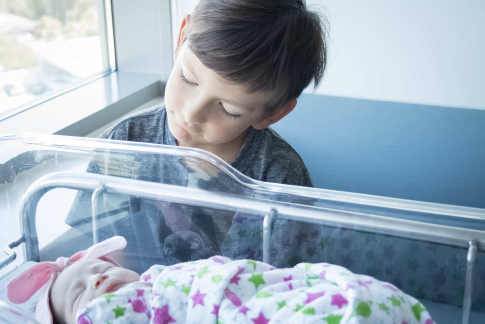 Big brother looking at newborn baby sister at Hoag Hospital-Bug and Roo Photography-Fresh 48 Photographer-Newport Beach-Orange County
