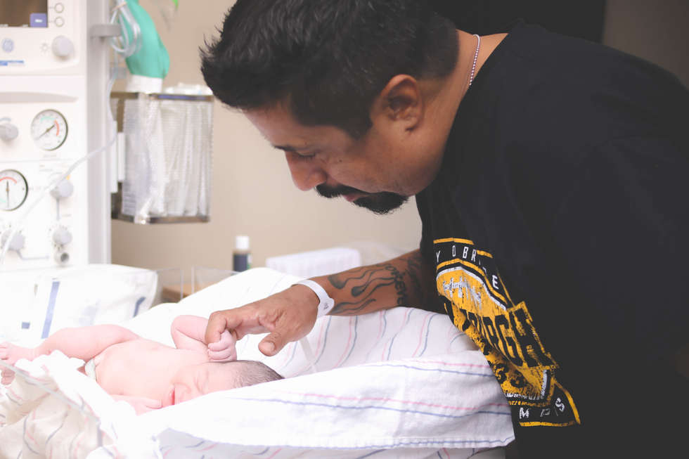 Dad looking his newborn  baby after delivering using Sacred Seed OC at Saddleback Memorial Hospital-Bug and Roo Photography-Labor and Delivery Photographer-Laguna Hills-doula-Orange County