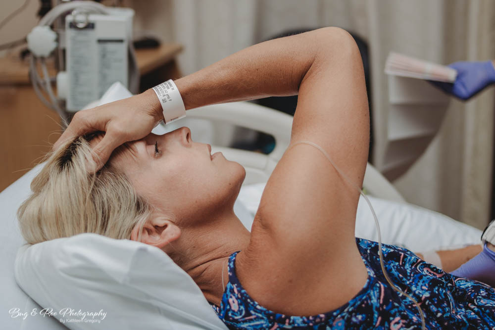 Mom holding head as she contracts during labor and delivery at Saddleback Memorial Hospital-Womens clinic-Bug and Roo Photography-Birth Photographer-Laguna Hills, Orange County