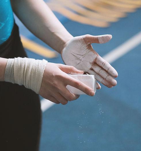 Twisters Gymnastics: Gymnastics girl chalking hands.