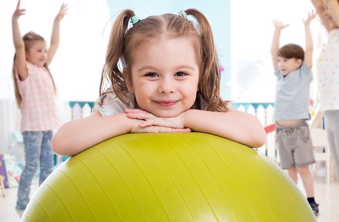 Assessment Based Learning Center: Smiling girl with pig tails posing with her hands under her chin resting on a lime green fitness ball.