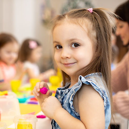 BES Pre-Kindergarten Program - Full Day: Preschool girl holding pink play dough and smiling at the camera.