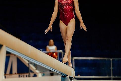 USA Gymnastics Competitive Girls Team: Girl gymnast on balance beam performing routine.