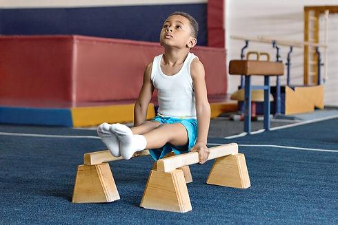 Twisters Recreational Gymnastics Girls & Boys Developmental Team: Young boy gymnast in an L-support on floor parallel bars.