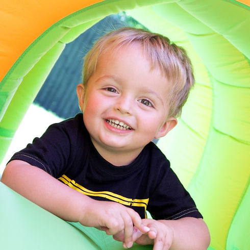 Terrific Tiger Two's: Happy blonde boy with brown eyes crawling through a soft play structure.