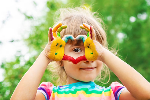 Berlin Activites Depot - Our Philosophy: Little girl peeking her eye the heart hands that are painted in bright colors and with smiley faces.