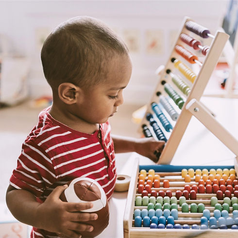 Assessment Based learning Center: Toddler boy playing with an abicus and holding a football.