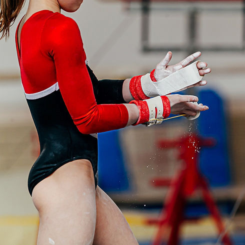 XCEL Gymnastics Competitive Girls Team: Girl gymnast chalking up to compete on uneven bars.