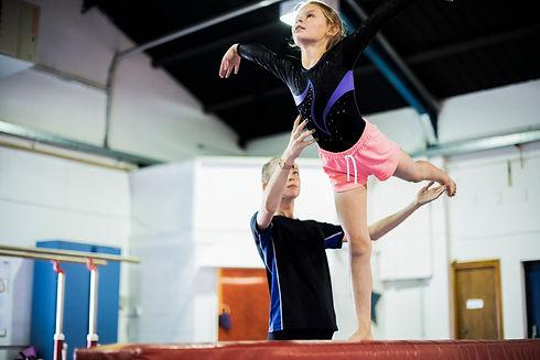 Twisters Recreational Gymnastics Program: Coach training young gymnast to balance.