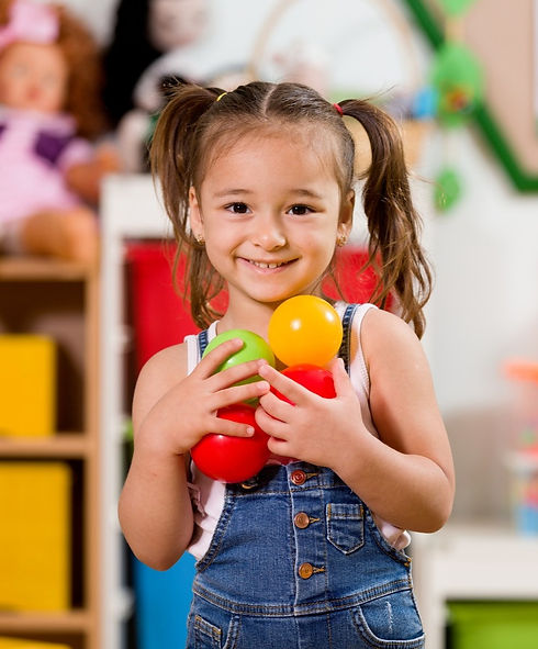 Berlin Education Station - Fully Accredited Learning Center: Happy girl holding balls in classroom.