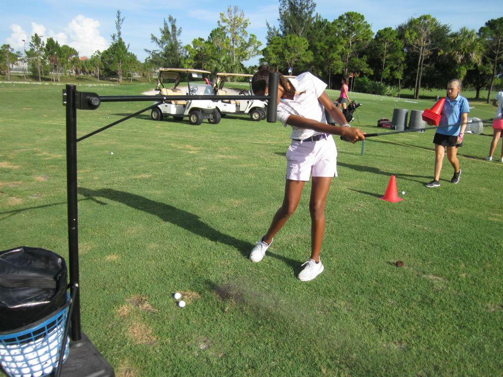women swinging golf club while utilizing pro head golf swing trainer