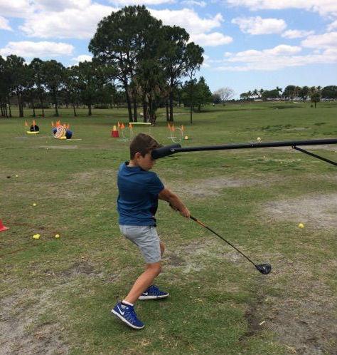 child swinging a golf club while using pro head 2 training aid