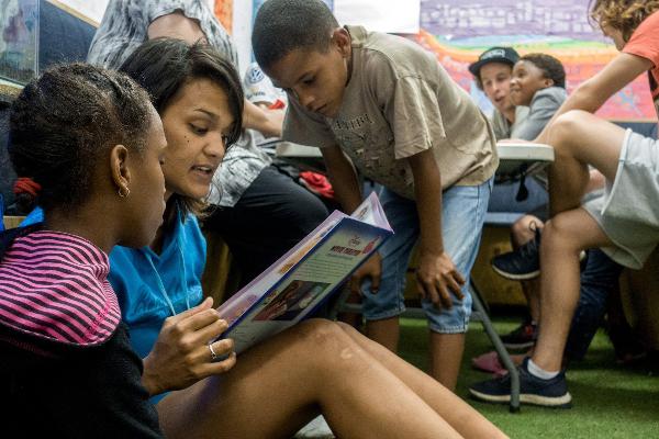 Eine Freiwilligenhelferin liest Kindern vor
