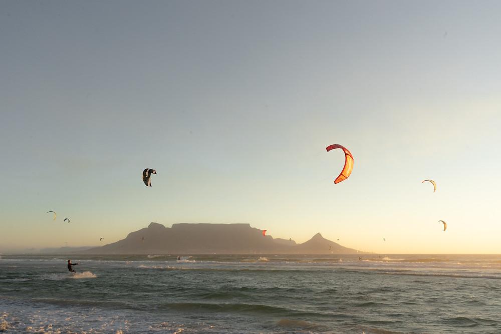 Kitesurfer surfen in Blouberg vor dem Tafelberg