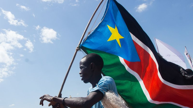 A man carries South Sudan's national flag at Mangateen Internal Displaced persons center in Juba on November 17, 2018. Sudan's civil war has led to the displacement of millions of people. Akuot Chol/AFP/Getty Images