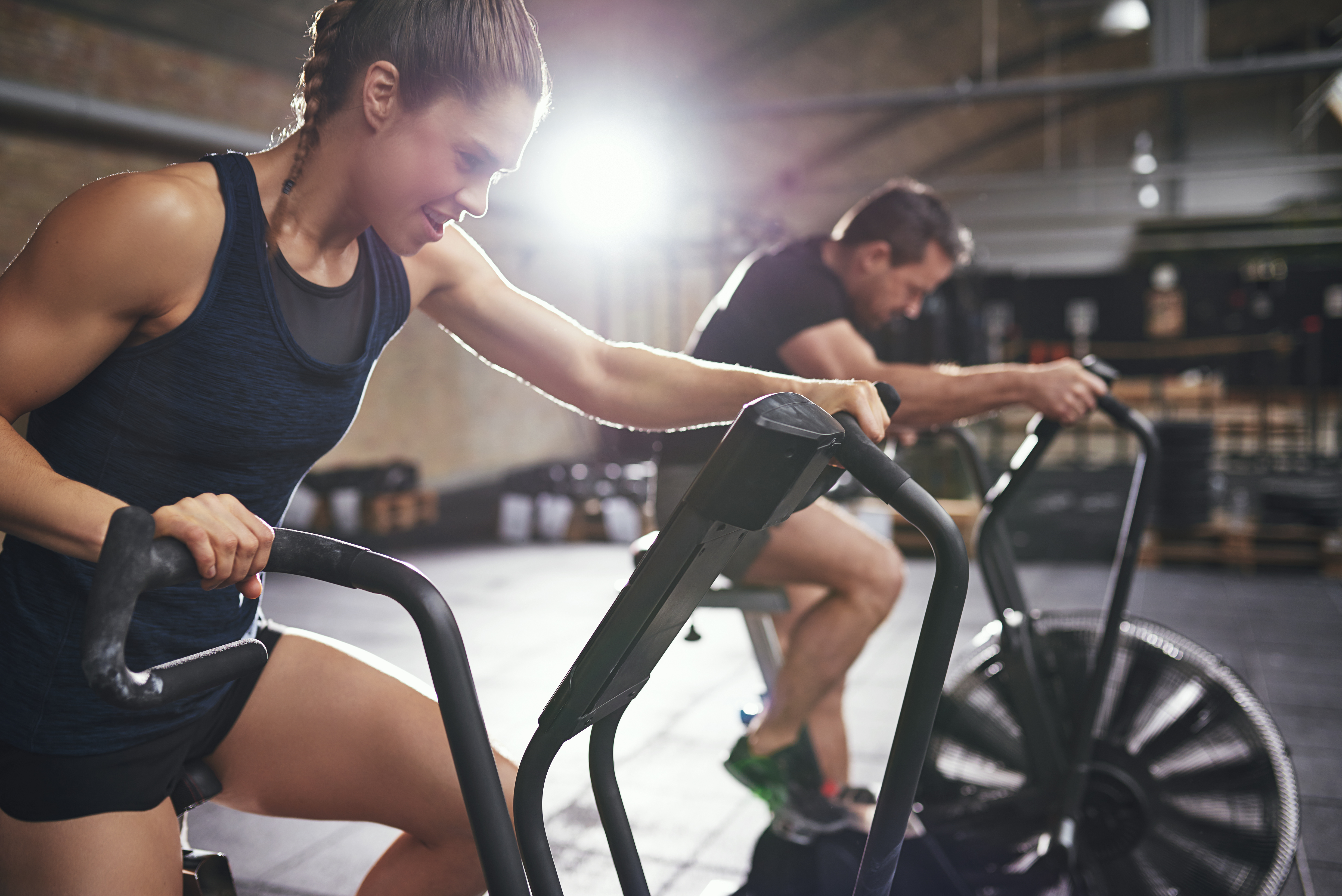 Young male and female wearing sportswear riding toughly cycling machines in light modern gym
