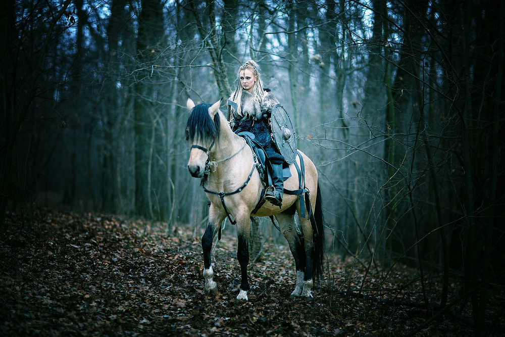 Female Shieldmaiden on horse in a forest. Wix photo.