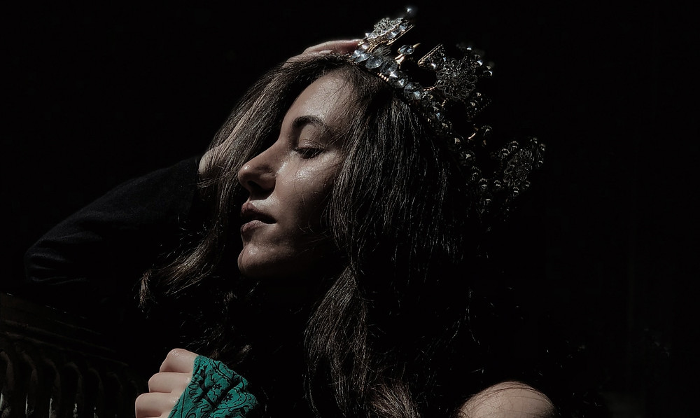 queen with a crown in a green dress