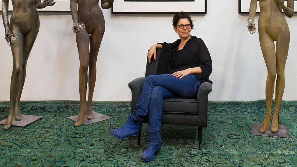 Owner, Katrien Van der Schuren, sittingin front of galleryframed artwork withcustom light fixtures mad out of mannequins by her side