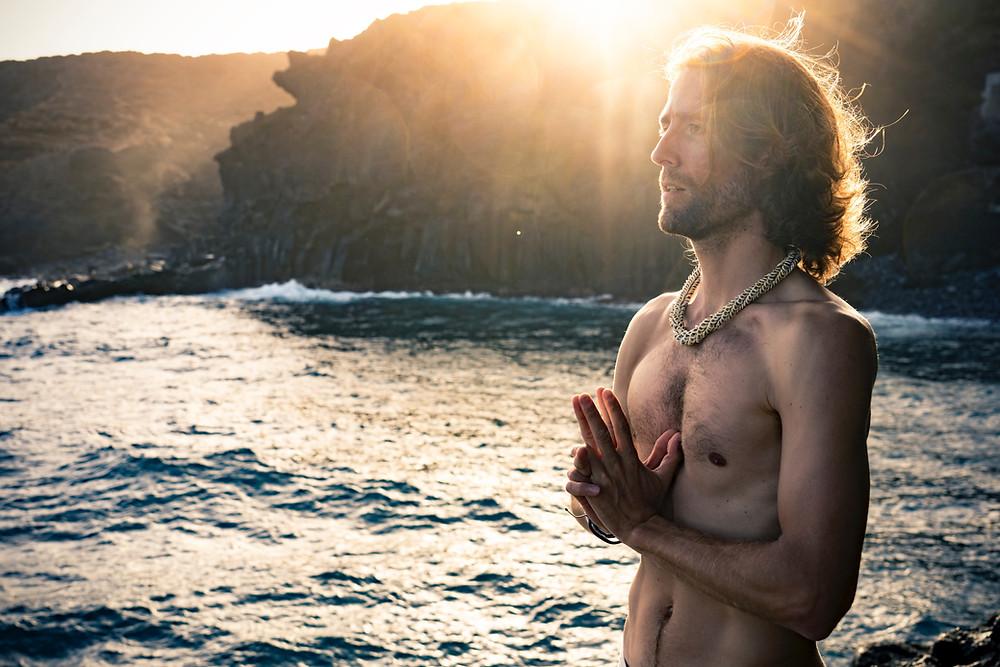 Mann mit nacktem Oberkörper steht am Meerufer mit Felsen und Sonne im Hintergrund