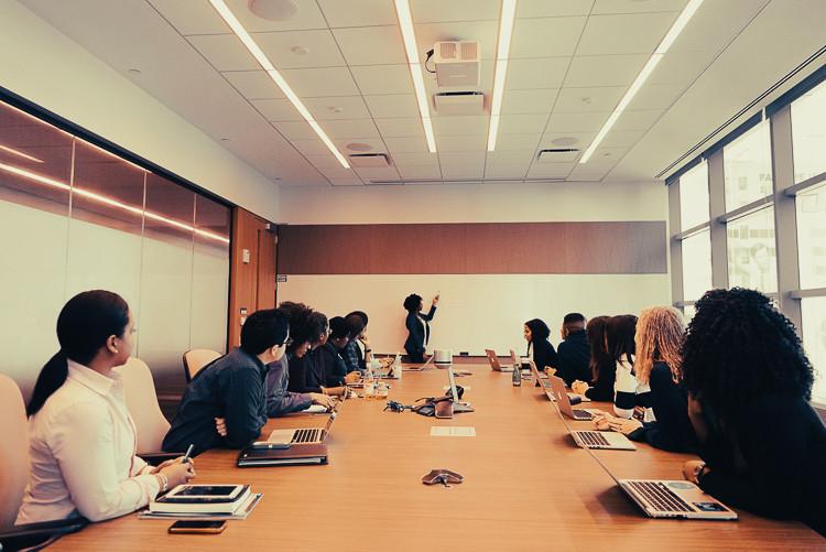 12 Menschen in einem Meetingraum mit Laptops auf dem Tisch die einer Sprecherin zuhören