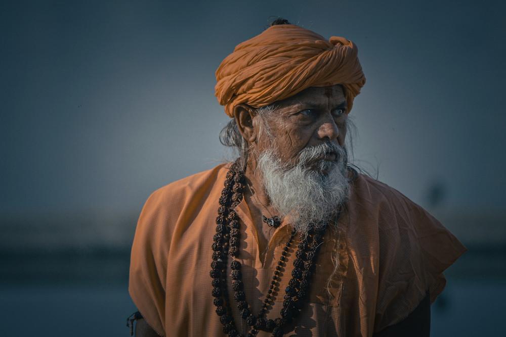 Indischer Guru mit orangenem Umhang und weissem Bart