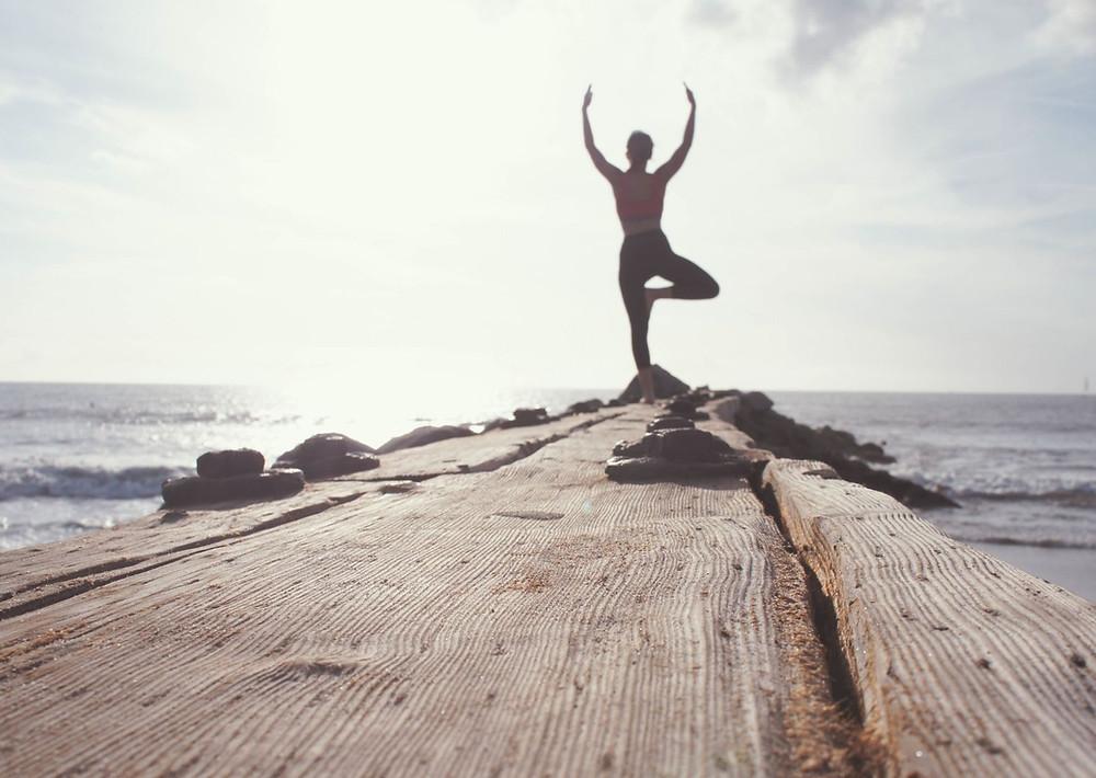 Ein Mann macht die Baum Yoga Pose am Meer