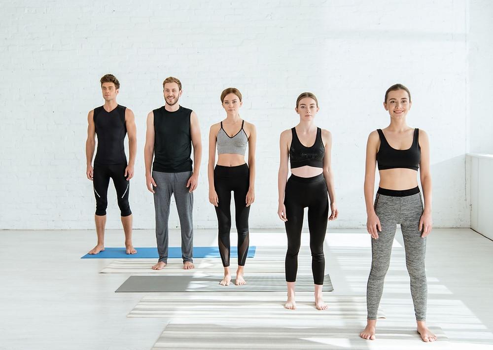 Zwei Männer und drei Frauen in der Yoga Pose Tadasana