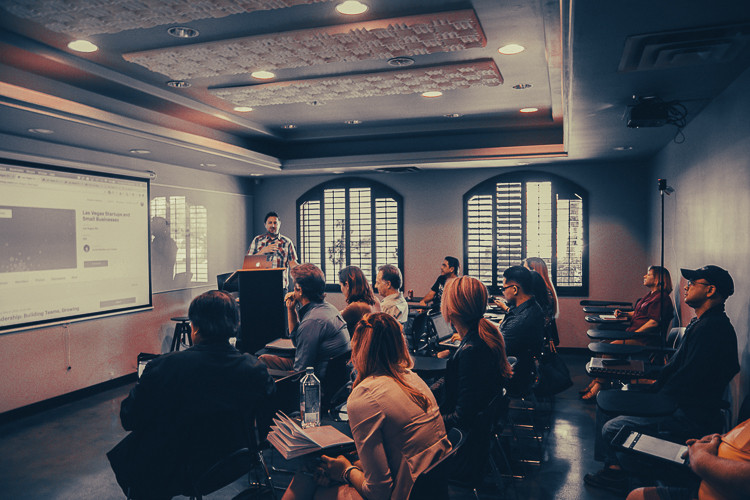 Ein Seminar mit mehreren Menschen in einen Raum die auf eine Leinwand gucken
